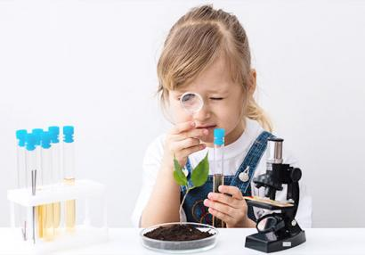 photo of a little girl playing with laboratory equipment