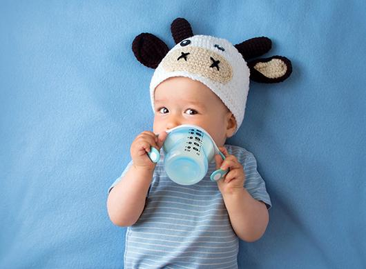 photo of a baby boy wearing a cow cap and drinking milk