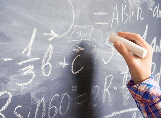 photo of a child resolving a mathematical problem on a blackboard