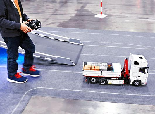 photo of boy playing with a remote-controlled truck