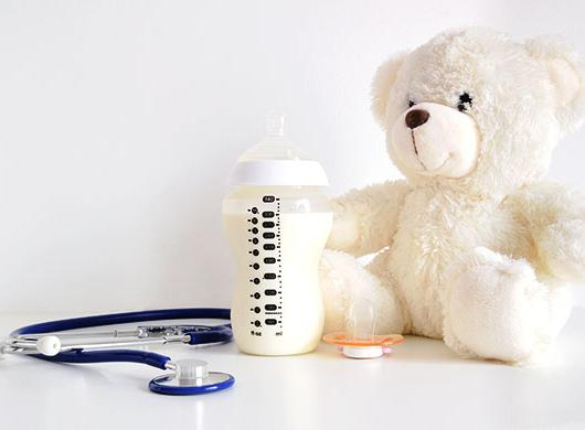 photo of a baby bottle, a teddy bear, a pacifier and a stethoscope